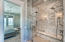 Elegant dual head marble shower with glass doors