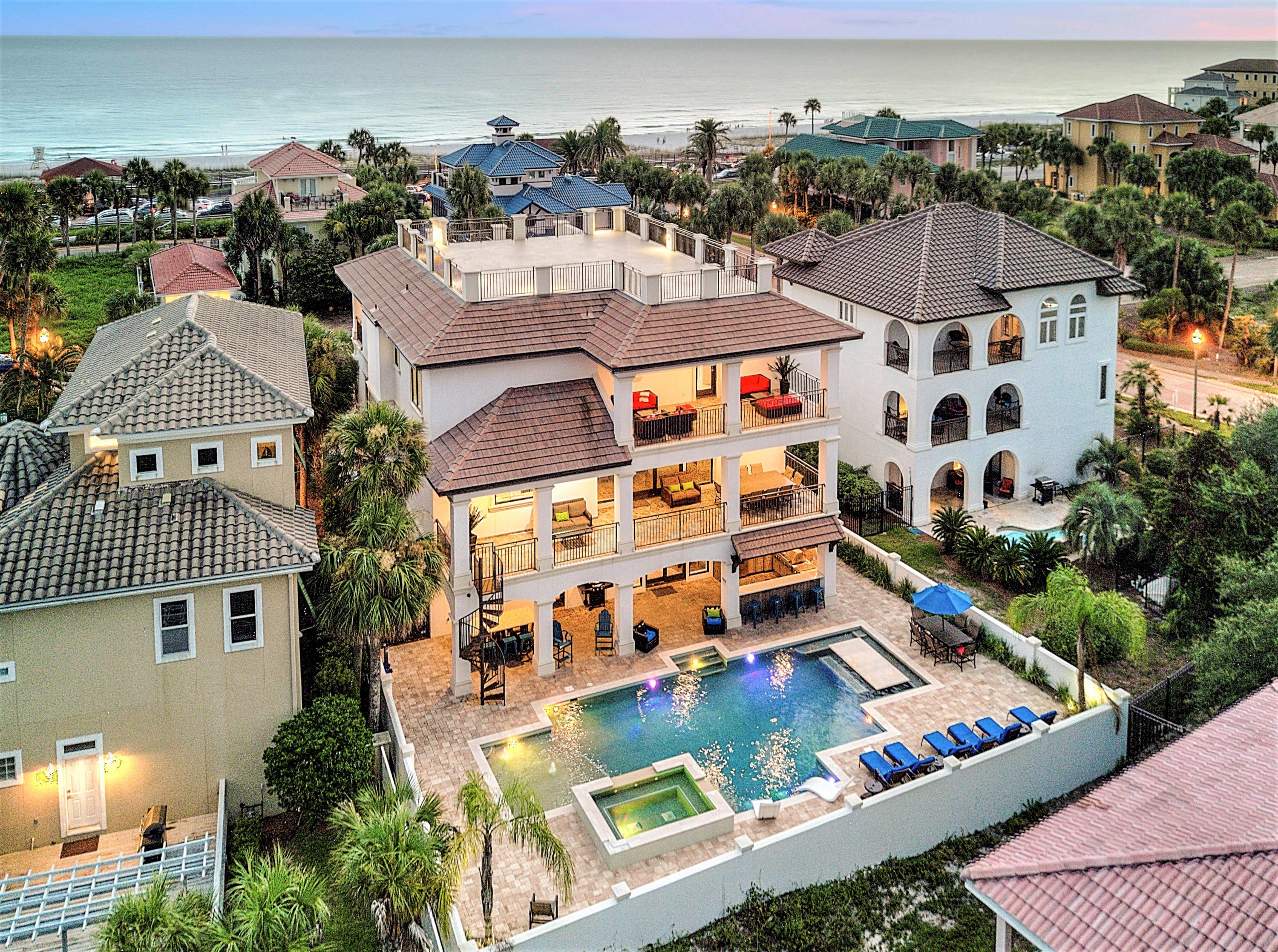 This exquisite 7 bedroom home just steps from the beach is what coastal dreams are made of! Located in the highly-coveted gated community of Destiny and sprawling across three levels, this home is thoughtfully designed to create the ideal beach house. The coastal contemporary design matched with the luxurious amenities provides maximum comfort, as well as functionality. This home encompasses 5,491 square feet of indoor living space and over 3,000 square feet of lush outdoor living space featuring a resort style pool and deck complete with a spa conveniently adjacent to the covered summer kitchen. Expansive balconies on the front and back of each level and a viewing deck above not only give you ample outdoor space, but provide exceptional views of the gulf and neighboring lake.