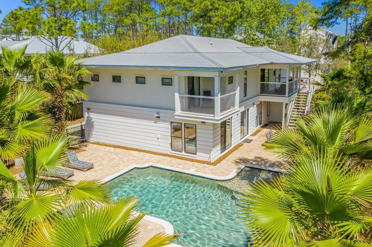 This Canal Street Beach Cottage, aptly named ''Beside Seaside'', is ideally located in Seagrove Beach just steps from Seaside, Public Beach Access and all that 30A has to offer on a coveted private lot! With approximately 3800 square feet, the 6 bedroom (+2 bunk room) home is ideal for a rental investment or a large family retreat. The exterior of the home is manicured with lush tropical landscape which creates a sense of privacy. The second level hosts the spacious kitchen open to the dining area and living room filled with natural light from the vaulted windows. In addition, on this level, you will find the owner's suite with private balcony, 3 guest suites and one of two laundry rooms. Level one provides 2 additional guest suites, 2 bunk rooms, a morning kitchen, the 2nd laundry room  and a gracious entertainment room for watching tv or playing games. As an added bonus, the layout of the first floor provides a separate entrance for the 2 bedroom/ morning kitchen area and may be rented as a separate lockout unit. The resort size outdoor sanctuary is surrounded by palm trees with chaise lounges with an outdoor dining and grilling area.  The 12,500 gallon heated pool added in 2016 is one of the largest in the area. This Beach House sleeps 16 and offers a 2 car garage plus expansive parking for all guests.