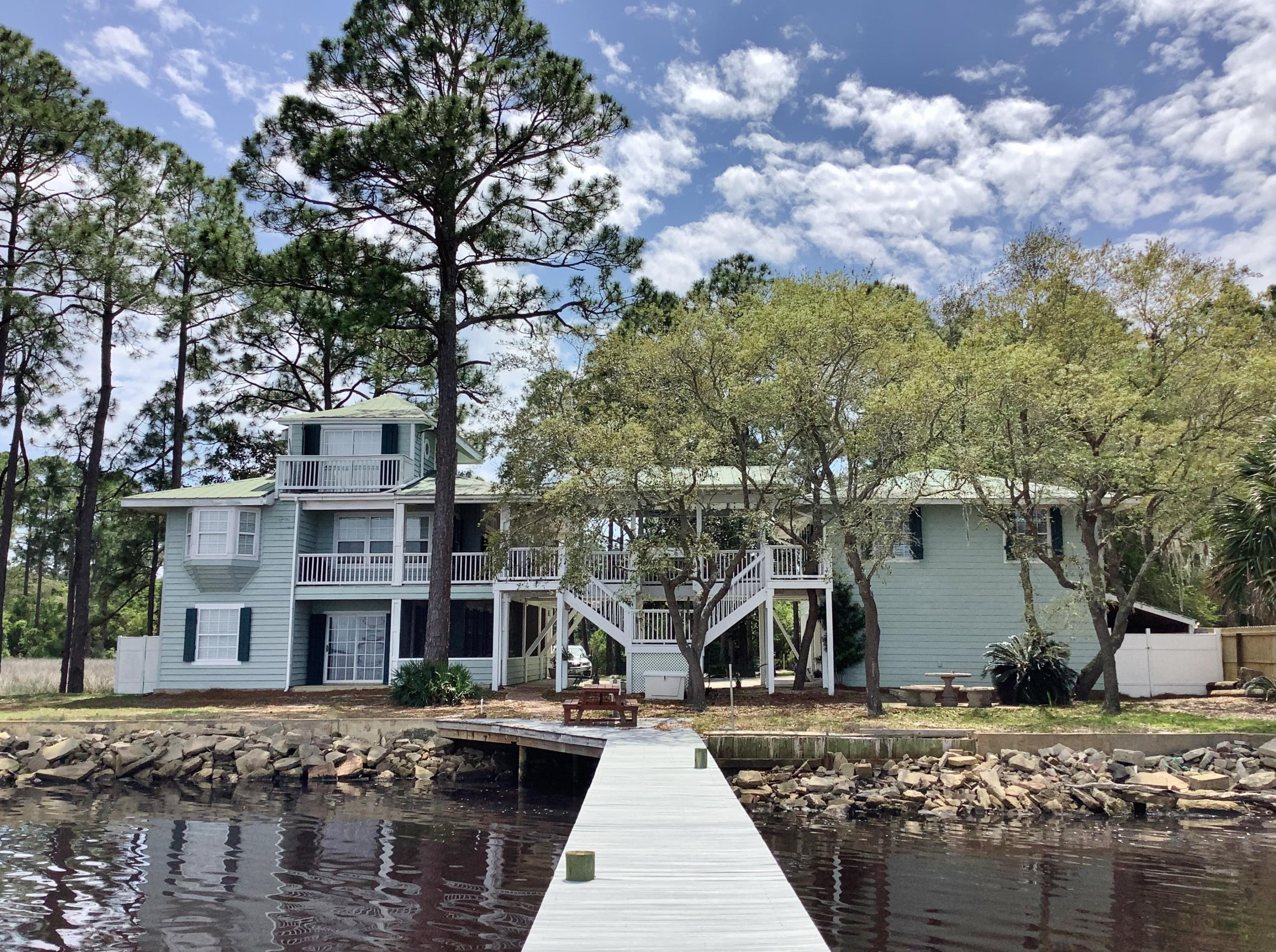 REDUCED! Boaters Paradise situated on a tranquil peninsula with 163ft of prime waterfront, private dock with lift, and intercoastal access. Lovingly known as 'The Bridge House' it's the vision of an award winning, mixed media artist, and her engineer husband with an affinity towards the water. A covered walkway connects main house to guest house, with expansive covered decks capturing  breathtaking views of the Bay. Designed for easy Coastal living with a flare towards Southern hospitality, guests and family have their private,1 bedroom, 2 bath Guest House with full Kitchen, Living and Dining Room. Main home is filled with special features and textures like solid Cypress floors, solid Wild Cherrywood Wall and breakfast bar, Solid Oak cabinets, a soaring ceiling surrounded by windows pouring natural light into the ensconced Loft, inviting Living and Dining area and kitchen with breakfast bar. Master bedroom has window seat with Bay window. Downstairs is a perfect artists studio, and/or another Living room, 2nd Bedroom and full bath, plus a laundry closet. Sliding doors go out to the Bay front patio. A wrap around screened in porch completes the main home. A 1 Car garage, plus workshop garage, has a washer/dryer hook up for the Guest House. Main home is made of solid Cypress wood with aluminum roof. Guest house is hardiboard siding with galvalume roof, built in 2001, featuring bead board accents, and bamboo flooring inside. There's a fenced camper parking corral, generous guest parking, and a marsh along 1 side where any number of beautiful birds can be found. The sunsets are unforgettable, with a painters palette of colors stunning to see over the distant 331 bridge as its backdrop. This Coastal compound on over 1/2 an acre at the end of the quaint, Non HOA, 10 home subdivision welcomes you in along a private drive with well groomed front yard, studded with Magnolias. A neighborhood boat launch is just across the way, with navigable waters through the marsh. The poss