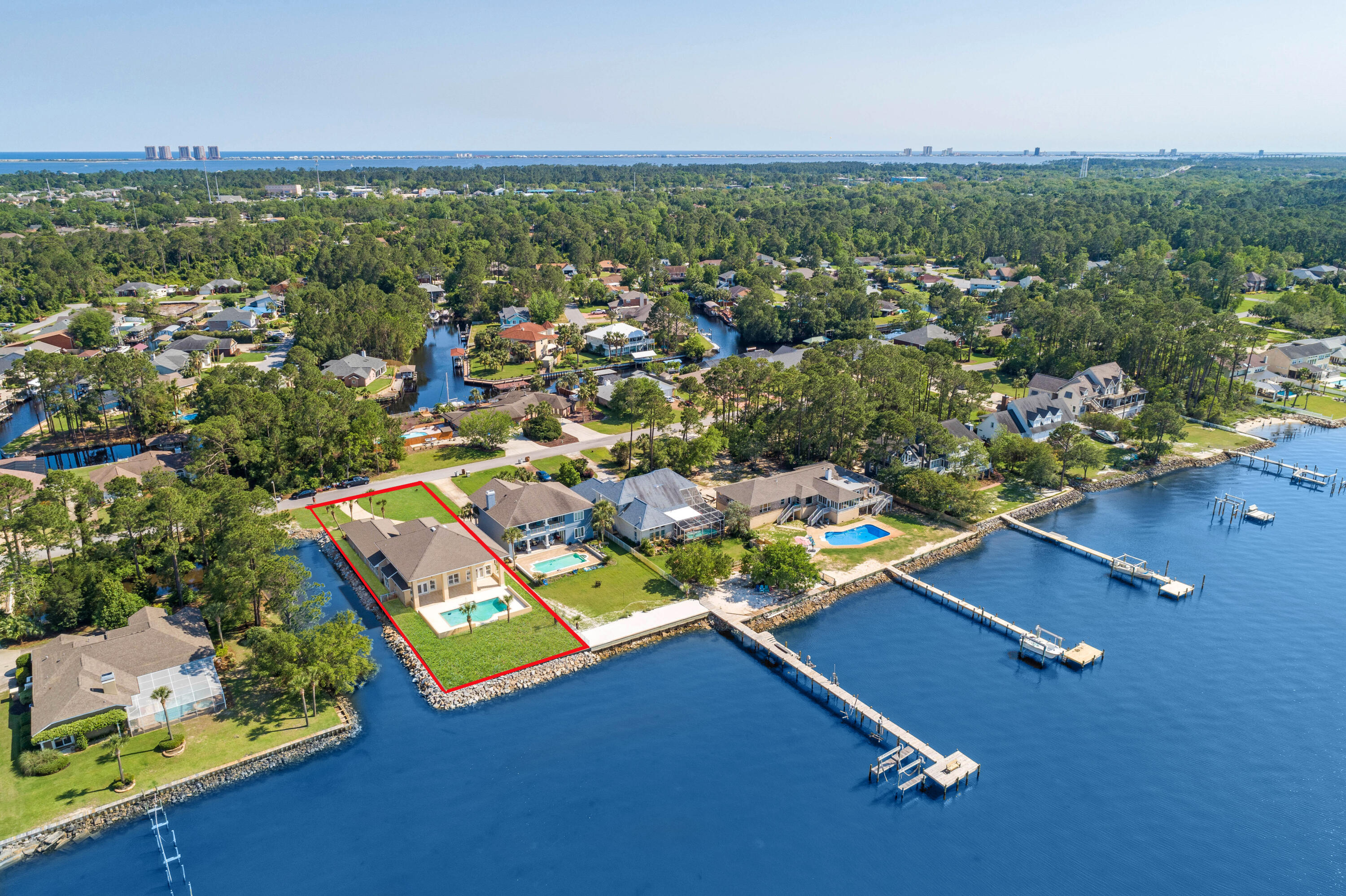 This regal waterfront estate resides on Pensacola Bay and offers a gunite pool with a 3 car garage and an open spacious living area. Embrace the ample natural light that floods into this gorgeous home with stunning water views from the entire living area. Ideal for entertaining, this home offers a sizable kitchen with a  formal sitting/entertaining area, formal dining room and covered lanai (47'x14'). Enjoy the resident dolphins that frequent the area daily and relax and enjoy epic sunsets from your backyard oasis. The kitchen comes equipped with custom cabinetry with pull out drawers, granite countertops, a plethora of cabinet storage and counter top space, double wall oven, 5 burner electric cooktop, prep sink, built-in desk and walk-in pantry. The primary suite has a separate entrance t o the lanai, dual walk-in closets and the bathroom has a walk-in shower with dual shower heads, garden tub, his-and-hers vanity with linen storage and a water closet. Upstairs you'll find 3 bedrooms and 2 bathrooms. Two bedrooms share a Jack-and-Jill bathroom and the 3rd bedroom makes for a great guest/in-law suite with a massive walk-in closet and bathroom with a walk-in shower and garden tub with abundant cabinet storage and water views. Other notables are BRAND NEW irrigation well and pump, plantation shutters, crown molding, over-sized laundry room with additional storage and utility sink, powder room for guests, additional  storage room in garage, pull down attic stairs, termite bond, hurricane protection, fenced back yard, child safety gate for pool, eve lighting and exterior ring camera. 160 tons of rip rap just added. Flood insurance is $550. Located in Gulf Breeze school district and just 7 miles to beautiful Pensacola Beach. Check out our full video tour on the MLS and YouTube.