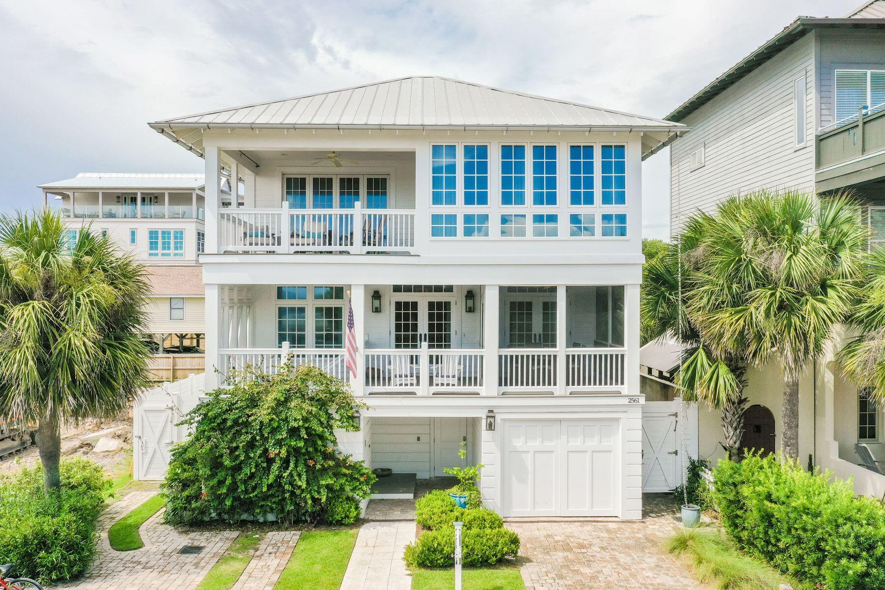 This magnificent beach home is one house from the beach with amazing views and an incredible outdoor living area with pool, spa, and lanai for the entertaining lifestyle. Steps from the white sandy beach, this prime located three-story home boasts breathtaking gulf views. This spectacular house was designed by renowned architect Sheldon Stone and interior designer Parker Kennedy in 2015. Four well-proportioned living spaces provide ample space for entertaining in style while guests can seek out their own quiet nook to relax or chat. White shiplap and soft nautical hues create a laid-back beachy ambience in a home designed for families and friends to come together and make memories. Floor-to-ceiling french windows bathe the main living area in natural light while gleaming hardwood floors floors add a sense of timeless durability. Entertaining is a cinch in the fully-equipped open-plan kitchen with all-white cabinets and granite counters. The center island breakfast bar is designed for hanging out with the chef. A sliding barn door hides ample orderly storage in the spacious walk-in pantry. Five upscale bathrooms and five bedrooms include a spacious bunk room. Wake up to shimmering gulf views stretching to the horizon from several porches and loggia. Step outdoors and enjoy Florida life to the full. Relax on lounge chairs beneath the gazebo and take cooling dips in the curving saltwater pool and hot tub. Life at the beach does not come more convenient, with a beach walkover directly across the street. Look forward to solitary early morning walks on the expansive wave-lapped sand and sharing stunning sunsets with those you love. Boutiques, al fresco dining and entertainment are plentiful in nearby Seaside.