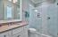 Private guest bathroom with custom tiled walk-in shower