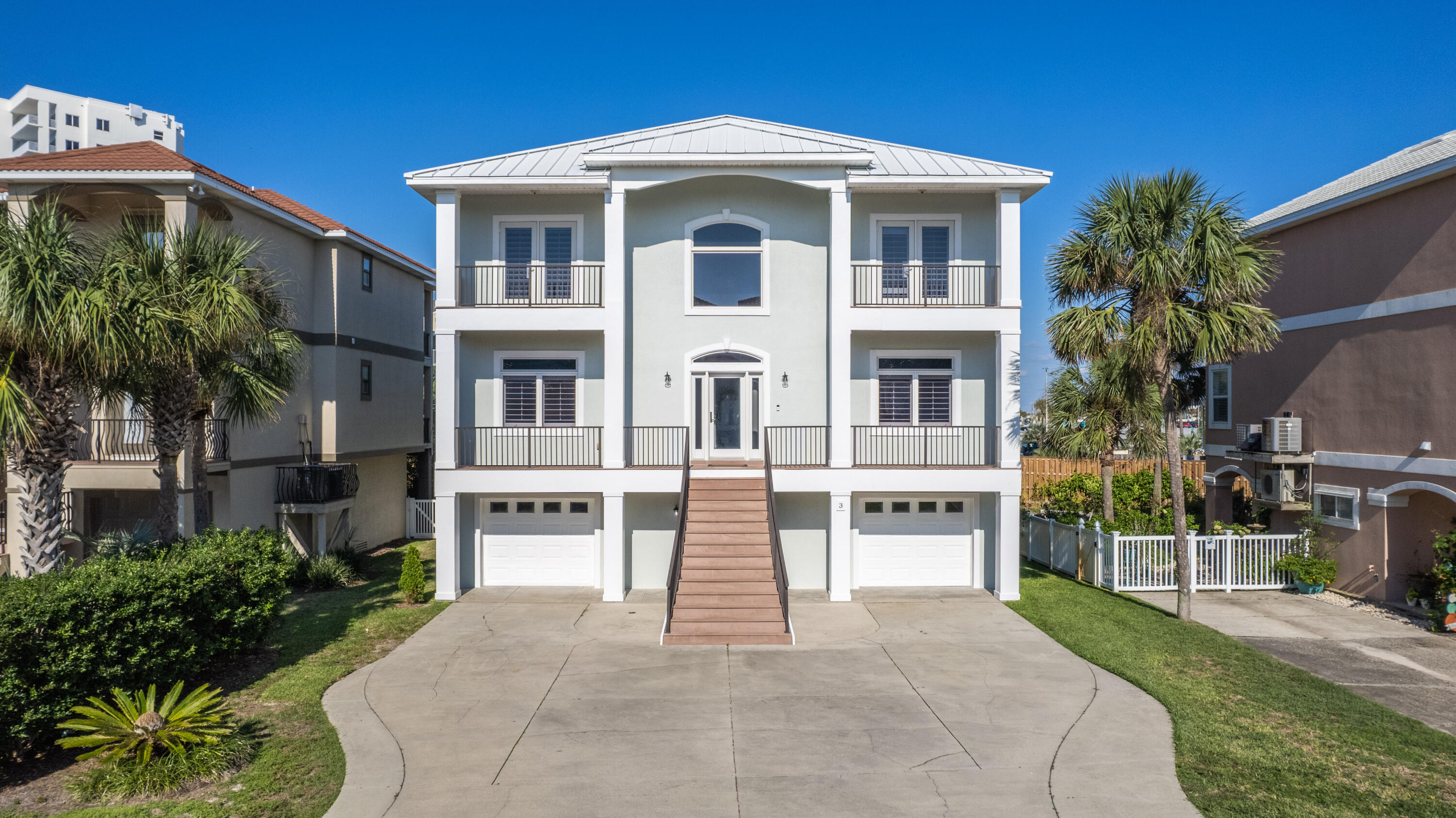 Conveniently located on Pensacola Beach in the private community of La Caribe, this gorgeous home offers an open spacious floor plan with 10 foot soaring ceilings and impact resistant doors and windows with fresh paint on both interior and exterior. Located on the ground floor, you'll enjoy an awesome climate controlled 1300+ sq ft bonus living area with a full bathroom and additional storage that is perfect for entertaining or even a pool room. With an optimal location, it's just a short walk across the street to Casino Beach (public beach access), the pier, Boardwalk and a plethora of dining and entertainment options all within walking distance. The main living floor has crown molding and travertine flooring throughout with all new tasteful light fixtures. The kitchen comes equipped with  granite countertops, stainless steel appliances, wall oven, island with a breakfast bar and a pantry. Just off the kitchen is the entry to the oversized partially covered balcony creating the perfect entertaining space. The third floor hosts the primary suite with bamboo wood flooring, large walk-in closet with separate dressing area. The primary bathroom has dual vanities, a walk-in shower, water closet and jetted tub. Enjoy Gulf views from the private balcony located off the primary bedroom. Other notables are plantation shutters throughout, Trex decking, new ice maker, and outdoor shower. Power source in garage to support a generator to power the entire house. Conveniently hop around the island via golf cart and enjoy all Pensacola Beach has to offer such as Fort Pickens, the National Seashore and miles of wonderful walking/biking paths. Since the neighborhood of La Caribe does not allow short term vacation rentals, you can enjoy your privacy and a peaceful community all year-round.  Enjoy great, full time residents in this sought after exclusive Pensacola beach community! Check out our full video tour on the MLS and YouTube.