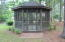 Screened Gazebo. It has a Ceiling Fan with light and electrical outlets inside.