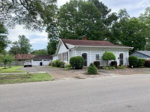 View from NW corner. Brick home with large front porch and detached garage.