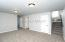 Lower level offers storage space under stairs, laundry room, full bathroom, and two bedrooms.