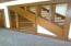 Shelving and stairway is open and exposed in the den.