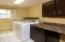 Upper-level laundry room with cabinetry