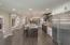Large column refrigerator, island with granite, induction range & vented hood, raised dishwasher & beverage cooler.