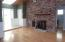 Living Room with brick fireplace and wood floors.