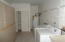 Large laundry room with shelves and cabinets for plenty of storage.