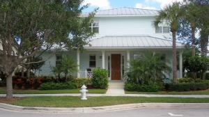 Front view of home with inviting large porch. Key west style with metal roof and tranquil sea blue exterior