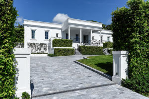 Front exterior with Italian marble driveway. Custom hurricane impact doors and windows throughout this completely re-built home situated on a high elevation.
