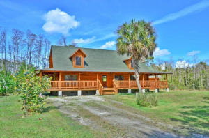 Sweet sounds of nature surrounds your charming, quality built Cypress log home situated on five plus acres. Featuring three bedrooms plus a spacious loft, open floor plan with a wood burning Tennessee rock fireplace in the living room, great working kitchen with maple cabinets, granite counters and stainless steel appliances, Australian Cypress wood floors throughout, Cedar lined closets, wrap around porch, upgraded electrical system plus, various fruit trees, an oversized two car garage with a storage area in the attic. Country living at it's best and yet so close to Golf , top restaurants, beach, airport and more..