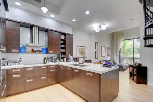 Beautifully upgraded kitchen with marble counters and large breakfast bar, upgraded cabinets, built in Sub Zero refrigerator, Miele Range and recessed lighting.