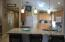 Beautiful updated warm wood cabinetry with neutral grani