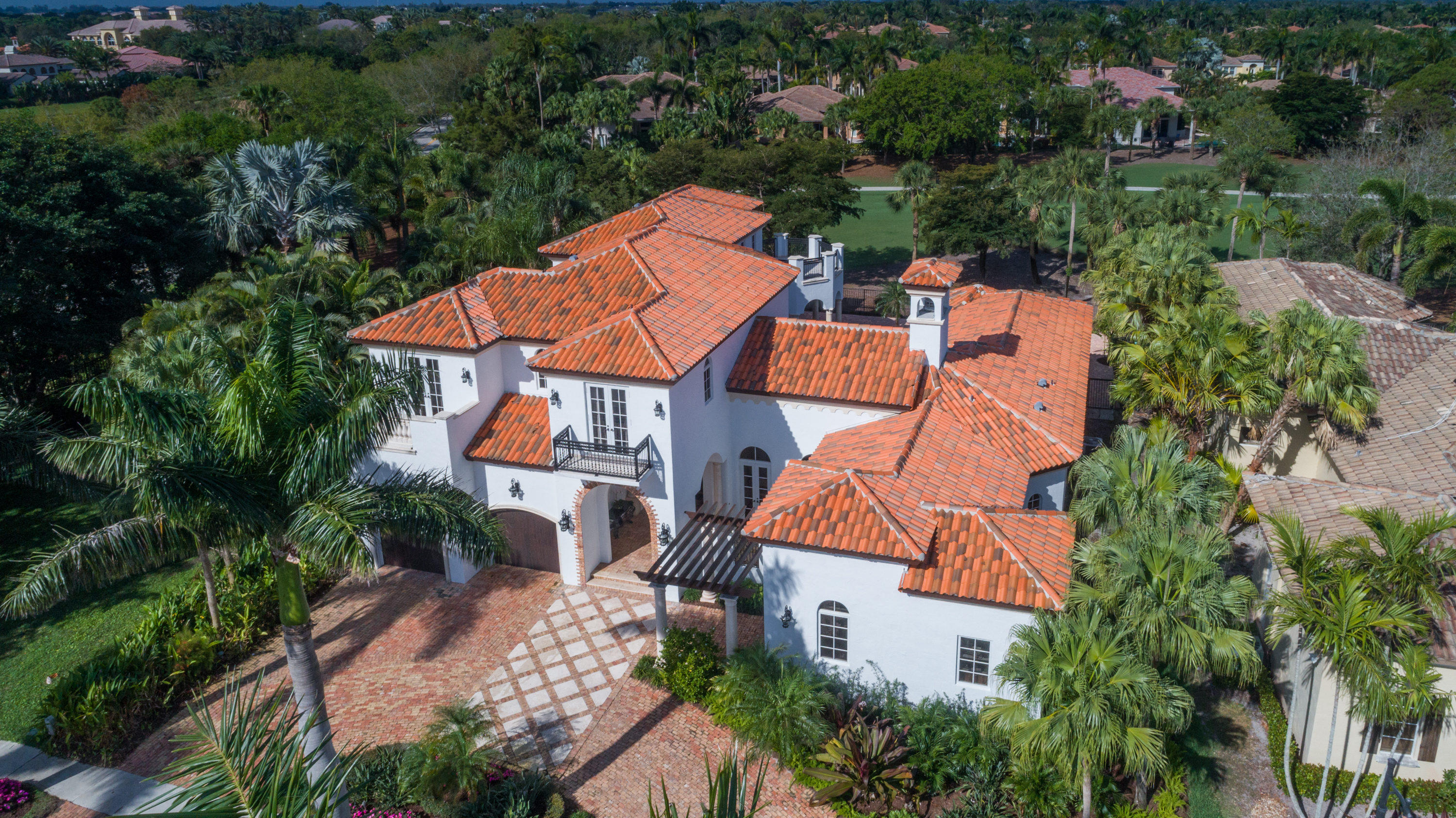 MOTIVATED SELLER. Situated on a corner lot with golf course views in the desired Capri section of the prestigious Mizner Country Club is this extraordinary residence of 4 bedrooms, 4.2 bath plus office and theater room. Custom built by Tuscan-Harvey Estate Homes, this home exhibits quality and elegance. When you enter you are greeted with soaring ceilings, a 700 bottle climate controlled wine closet, and a rounded staircase, with beautiful Spanish tile inlays, leading up to the second level. The formal living room with 6 foot stone mantle fireplace and cypress wood ceiling is sided by sets of french doors leading to a quiet fountain area or the custom beach entry pool and newly landscaped gardens. Custom built-in wood office is downstairs, making it a perfect place for quiet work or study. Dine in the formal dining room with arched windows and a butler pantry with a warming drawer. Chefs dream kitchen with large center island, Viking 6 burner gas stove, Sub Zero fridge, and lots of granite countertop space. The upstairs bedrooms offer plantation shutters and outdoor access with french doors & private balcony. Exit the home to your own tropical paradise. Redone patio/pool deck includes a summer kitchen and a heated beach entry pool that has a separate waterfall spa to refresh and relax all year. The 500 gallon propane tank operates the pool heater, grill, home generator and Viking oven/stove.