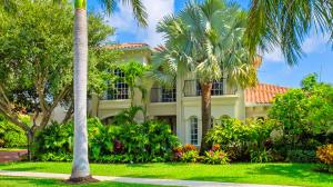 Mature Royal Palm Trees, Live Oak Tree, Bismark Palm Tree frame this Mediterranean-styled home