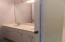 Cabana bathroom with 2 sinks and separate toilet shower area that leads to screened patio and pool area.
