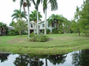 Great landscaping with pond and palm trees in front of the house