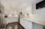 Custom kitchen with flat-screen TV, stainless appliances and petit bar