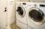 Inside laundry room with front loading washer and dryer plus pedestal drawer storage