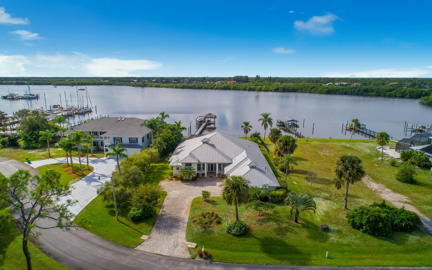 Discover this newer, custom, custom, custom Key West style wide waterfront luxury pool home with no expense spared! Special dockage with Tiki hut & 12,000lb lift will accommodate 3 boats! You will love the 12 & 13 ft coffered & tray ceilings, your gourmet kitchen with slab granite countertops, walk-in pantry + Kitchenaid & Bosch stainless steel appliances + a double wall oven & 5 burner cooktop! Custom wet bar for parties + an amazing entertaining screened patio with fabulous summer kitchen + gas heated spa + luxury pool! Elegant master bath with jetted tub, separate shower with dual shower heads & granite countertops! Solid CBS construction with concrete hardiplank siding, impact windows + roll down shutters on patio! 3+ car garage! A must see! Fall in love today!