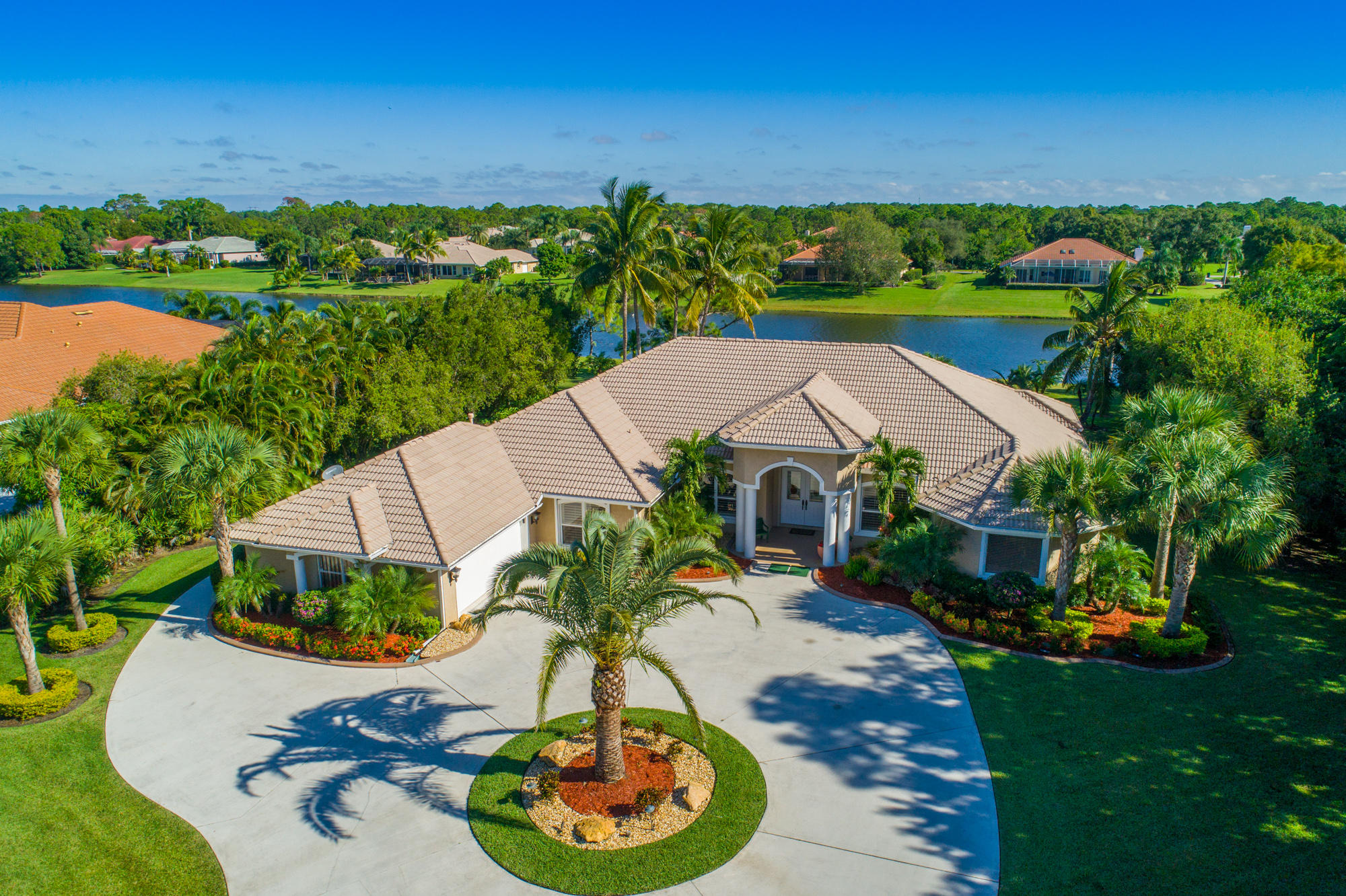 Absolutely Stunning Re-done beautiful home in Sabal Creek in PGA Village on 1.39 Acre Estate lot with lake view.  This CBS, Barrel tile roof, circular concrete driveway starts with new landscaping, exterior lighting & great curb appeal. Features 5 BR's, 4 Full BA's, 3 Car garage with 2 CG side load & other door left side of house perfect for the golf cart. Enter into magnificent new porcelain tile flooring, volume ceilings, design colors, custom window treatments,  gorgeous lighting, fireplace, decorative moldings & finishing details.  Gourmet Eat in Kitchen offers 42'' new white wood cabinet doors,  Carrera quartz counter tops, large island, new upgraded hood, tile back splash, butlers pantry, pantry in kitchen & walk in pantry down hallway.  Over $100,000 in improvements!  SEE REMARKS! Gorgeous Master Suite offer wonderful lake view, vinyl flooring, plantation shutters & large walk in closets with built in's. Exceptional updated Master Bath looks like a model! Separate shower, tub, dual sinks & quartz upgrade throughout. Fabulous outside area features phantom screen enclosure, paver extended patio, trellis & pool/spa fenced in with tranquil lake & tropical garden setting. This home is like paradise with all of the up to date decorating & design finishes.