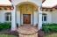 Beautiful brick walkway entrance through covered archway, scrolled lighting and double doors