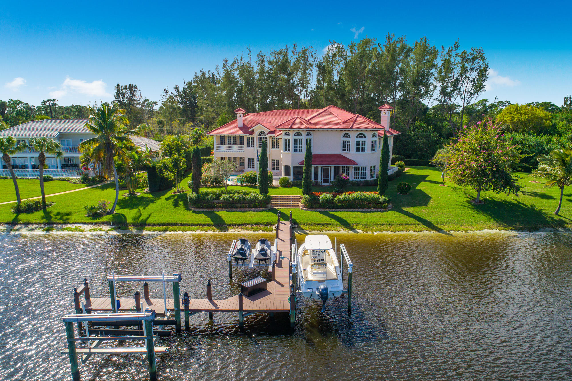 DEEP WATERFRONT ESTATE! Discover this MAGNIFICENT home located on the Saint Lucie River with dockage for multiple boats. This very private TROPICAL OASIS is built with the absolute finest of finishes. With just under 7500 under air living square feet, there is room for the entire family plus guests. The home is loaded with upgrades which include Marble flooring, incredible crown molding/trim details, soaring ceilings, surround sound with multi zones, balconies over looking the beautiful wide water view, enormous 85KW whole house generator, corner lot for privacy, impact glass windows and doors, 3 car garage, and so much much more! This home has approximately 239 feet of river frontage and a tropical landscape to die for that is impeccable maintained. The home also features a large screened in patio to relax and unwind on. Bay St. Lucie is a Luxury Gated Community with large estate homes in every direction. Do not miss this incredible opportunity to live your best life...