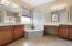 Master Bathroom has separate wood vanities, Roman tub, and glass-enclosed shower