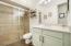 Ground floor bathroom has glazed wood vanity and upgraded tile