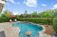 Custom saltwater pool with marble paver deck and privacy hedges