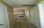 3rd bedroom closet on left, hallway that leads to utility room on right and porch. Kitchen at back center of photo