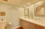 Remodeled guest bathroom with double sinks and quartz countertop, high hat lighting