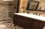 Renovated guest bath with bronze glass enclosed shower and fixtures