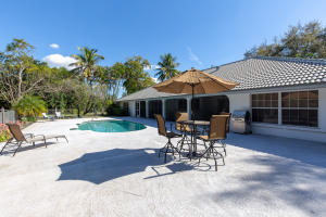 SPRAWLING POOL DECK WITH VIEW OF SCREENED LANAI AND REAR OF HOME