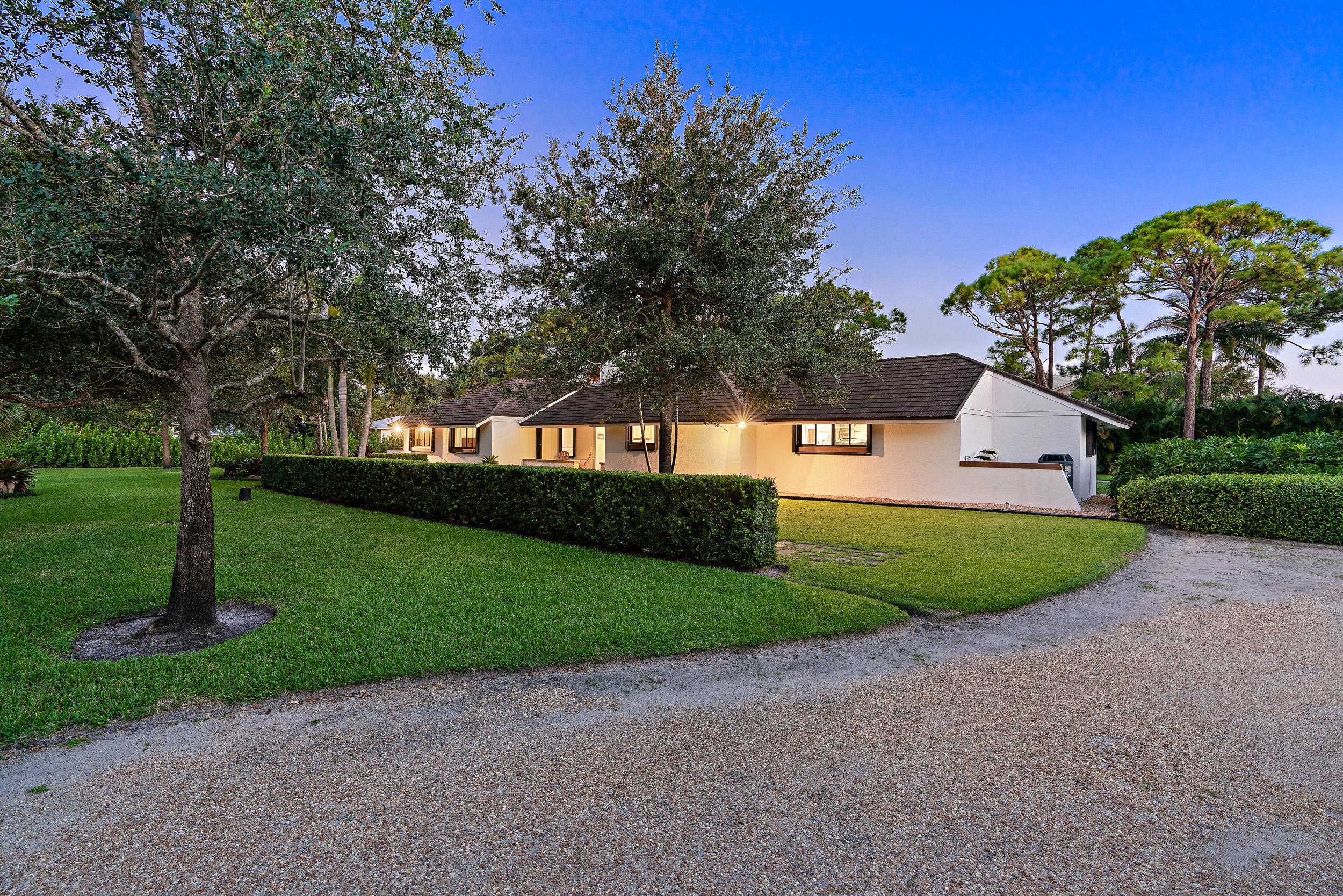 IMPECCABLE single-story CBS (concrete block construction) pool home located off the highly sought after Loxahatchee River Road! Situated on 1 FULL ACRE of land (!!!) and with a brand new pool, 50 year+ metal roof, lush custom landscaping, and impact windows, this home will check every single box of your search criteria and more! 6422 Fox Run Circle will sweep you off your feet from the moment you set foot on the HUGE property and enter the home's front door! Enjoy an expansive open layout with vaulted ceilings, charming wood beams and millwork, beautiful 20 inch Coquina coral tile flooring throughout, and a real coral stone fireplace. You will love the newly renovated modern kitchen featuring gorgeous tile backsplash, executive cabinetry, quartzite countertops, and [click to read more]   Kenmore Pro double ovens. This custom chef's kitchen boasts ample storage and space with a spacious pantry and a cook island. --- Retreat to your master bedroom to find a sprawling suite with soaring ceilings complemented by wooden beams, and an ensuite with a custom, real wood vanity, a frameless shower, and a linen closet. --- The backyard at 6422 is the perfect place to relax and enjoy the South Florida tropical climate with a new sparkling, salt-water swimming pool with lights and PebbleTec completed in 2017 by RHR pools. With its extensive, lush landscaping with clusia and areca palm trees, fountains and custom cabana bath with a walk-in shower, you'll want to spend every moment in your backyard soaking up the sun and hosting friends and family for pool days and barbecues. --- Other features you will love about this home are the huge laundry room, extensive closet space, a spacious two-car garage and 400 Amp Service Panel for electric. This home has a $45k stone-coated metal roof from 2012 with a 50-year warranty. The 2 ACs are from 2014 and are under a 10-year warranty and its 2 tankless electric water heaters are also from 2014. The home is on well water and a water softening
