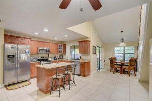 Open concept kitchen, with granite counters, dark wood cabinets, stainless steel appliances.