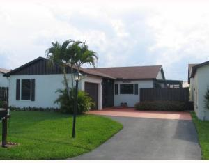 Biggest model on beautiful canal lot.  2BR 2BA with garage in hugely popular 55+ community. Shows great.  Beautiful remodeled kitchen, fantastic glass enclosed Florida room. Screened patio off kitchen for al fresco dining and grilling. Tile floors. Lushly landscaped, with mango, avocado and banana trees. Lot can be fenced- bring all of your pets! Low HOA fee includes basic cable and HBO, and lawn watering. Picturesque tree lined streets, waterfront pool, walking promenades around two lakes, tennis, and more. Walk to shopping, restaurants, close to beach, highways and airports.