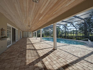Expansive Brick paver covered patio & pool deck with screened-in pool