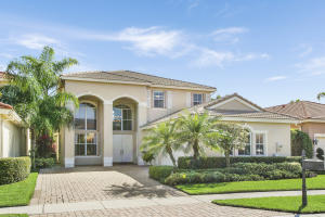 Front exterior with wide decorative paved drive and three car garage with windows for natural light.