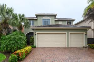 Front with paver driveway and three car garage and accordion shutters