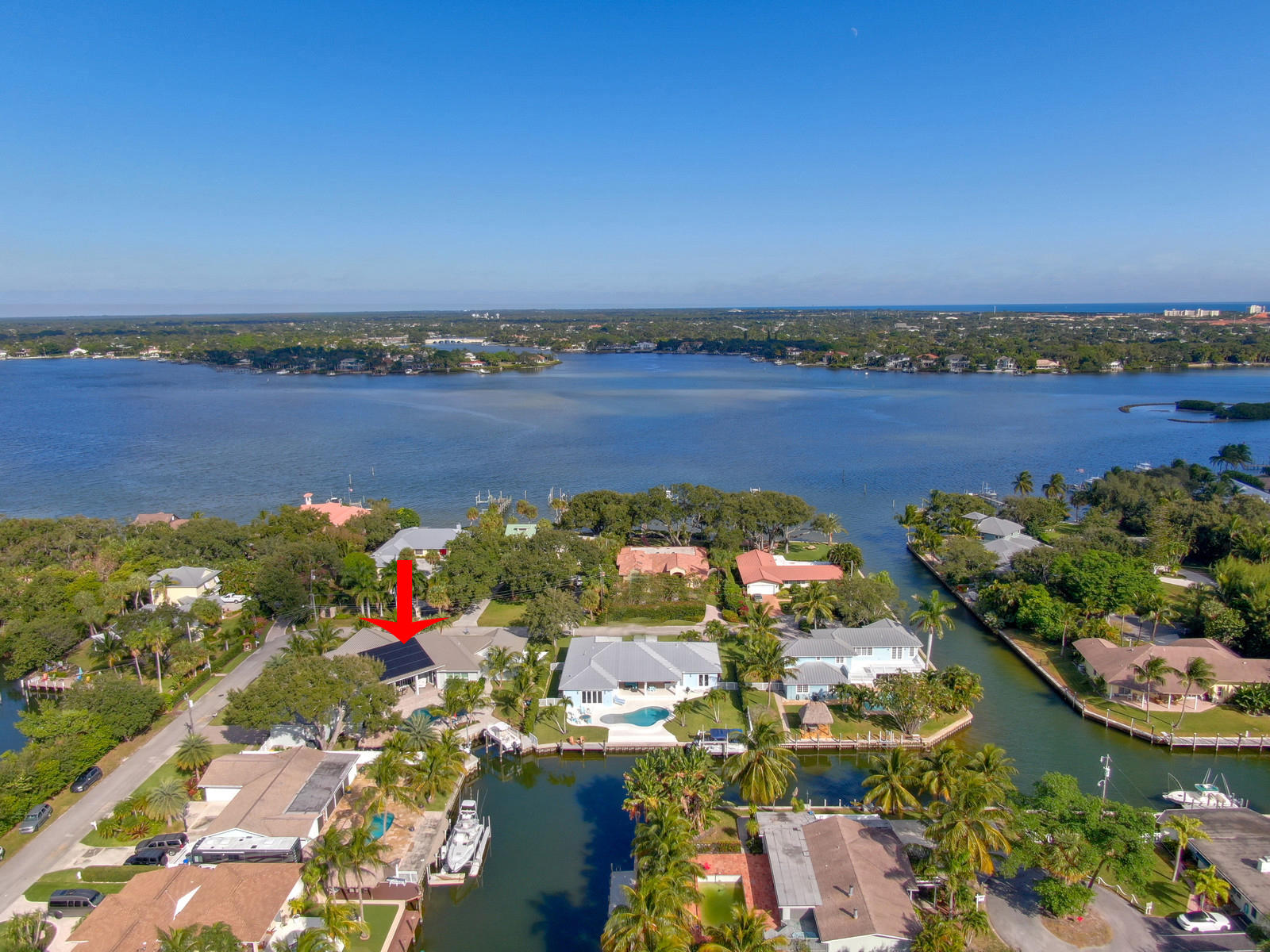This Spectacular, custom-built waterfront home with ocean access will have you in the Atlantic in minutes. This personal builder's home checks every box that a buyer is looking for. Located on a corner lot and built in 2017 with no expense spared. The coastal designed home sits on a .47 acre lot with a 10,000 pound boat lift and jet ski lift. Mesmerizing views through expansive 10ft tall hurricane rated sliding glass doors in the great room. This 4 bedroom, 3.5 bathroom home with 4 car air-conditioned garages boasts designer finishes, stunning vaulted beamed ceilings, and unsurpassed craftsmanship throughout. State-of-the-art Smart House automation gives you total control over your home. All CBS construction, metal roof, 11.8kw PV solar system, Hurricane impact windows, and doors. For the gourmet cook, the kitchen offers a large island, custom cabinetry made by Woodlife Custom Cabinetry, top of the line taj mahal leathered quartzite countertops and Jenn Aire appliances. The master suite includes his and her custom closets and overlooks the water and pool area. The large master bathroom features dual sinks, a separate shower and stand alone tub, custom lighting, marble flooring, and walls. Step outside and enjoy the Florida lifestyle with a large covered front and back porch, a Tiki Hut, Paddle Board Tiki rack, professionally designed landscaping by Steve Parker from Parker Yannetti, and a magnificent custom-designed heated pool and spa with a sun shelf, LED lights, and water features. Boating, fishing, paddle boarding is right in your backyard with a newly designed seawall that allows easy access to the water. The fixed boat lift should support up to a 27ft boat and with lift changes up to a 34ft. In addition, the small-vessel swiveling lift holds a WaveRunner. A-rated schools and minutes to great restaurants, shopping, golf, and pristine beaches.