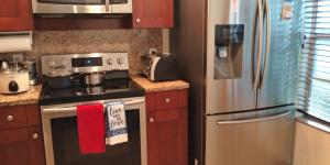 STAINLESS STEEL APPLIANCES + NEW WOOD CABINETS AND TILES