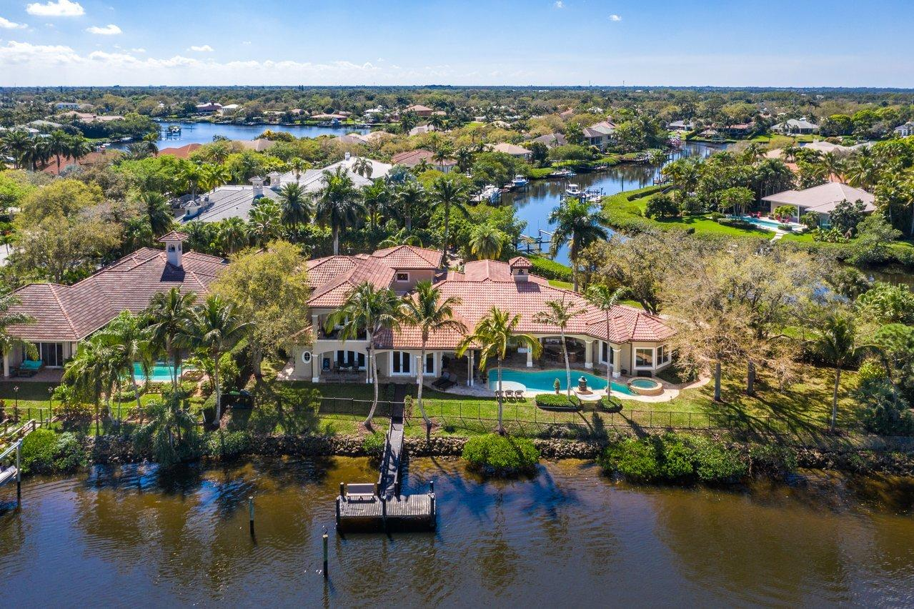 18669 SE Palm Island Lane. Boaters paradise with 2 docks and ocean access! Impressive waterfront home for sale in Jupiter River Estates (AKA Islands of Jupiter). Just a short drive to Jupiter Beach, Juno Beach Park and the shops, restaurants & nightlife of Harborside. Custom-built, spacious layout with 5 bedrooms, 5 full baths, pool and 3-car garage. This expansive property situated on over 1/2 acre lot has multiple indoor and outdoor spaces to retreat to. Designer kitchen with top of the line appliances, butler's pantry, game room with bar, exercise room. High ceilings, beautiful marble flooring, impact glass throughout and amazing river waterfront views! Separate living space with full kitchen on the 2nd floor provides flexibility for in-laws, guests or nanny. Outside, enjoy water views while relaxing on the patio with heated pool. Providing 2 docks, a boat lift and approx. 280 ft. of water frontage on front and back of house, you'll be living the South Florida lifestyle you've been dreaming of. Call us today to set up your viewing of this beautiful home!