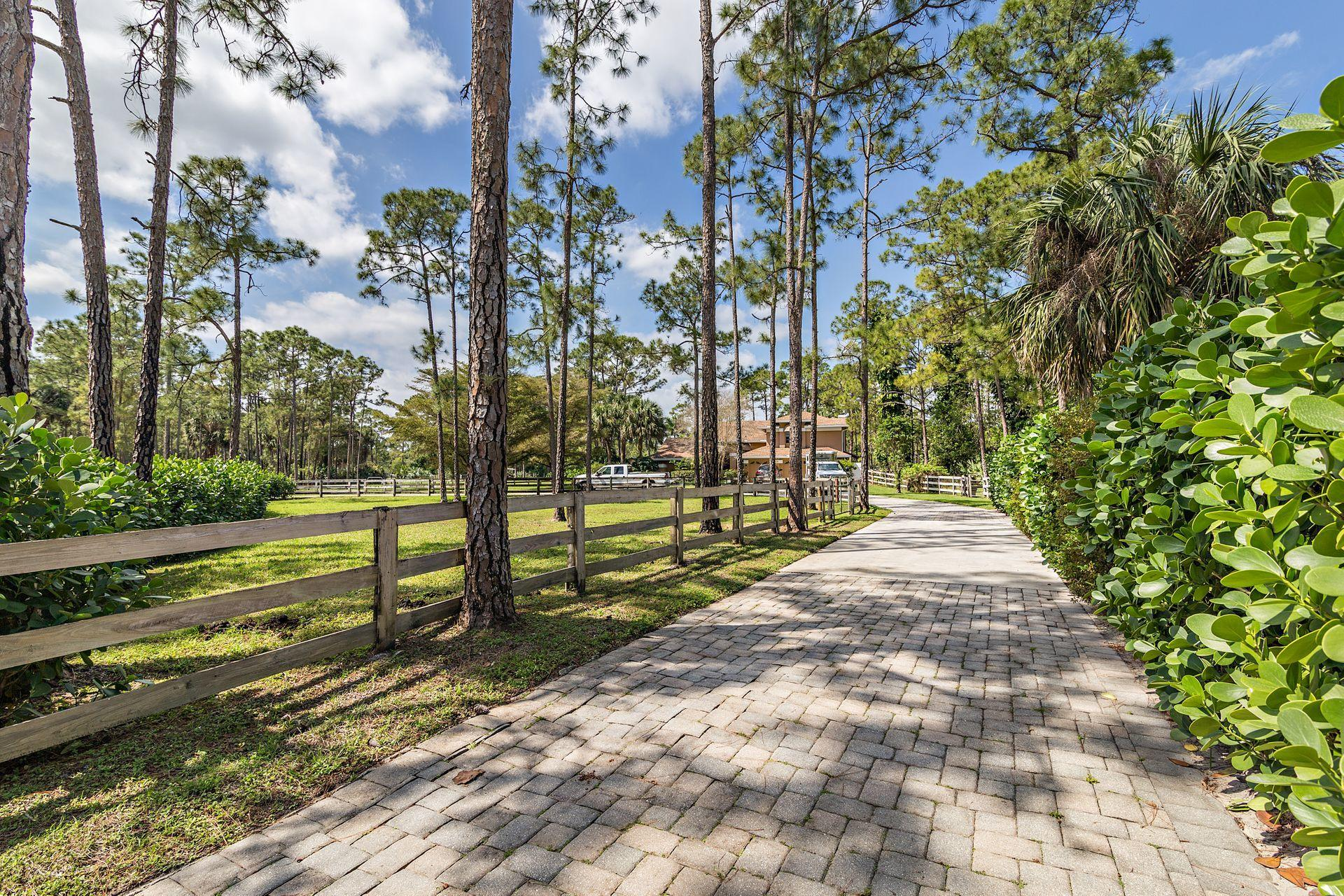 All sizes approx, Beautiful 10 acre equestrian estate impeccably maintained. This property has every equestrian amenity that a professional or serious amateur rider could desire. 10 stall main barn, two run in sheds with a total of 5 stalls plus two grooming stalls. Two tack rooms, one with sleeping quarters, kitchenette and bathroom. Large feed room, two office areas one equipped with spacious living quarters!  Barn has its own washer and dryer! Auto waters in 6 stalls, run in paddocks off 7 stalls. Fly spray system and newer water system. Beautiful dressage arena that is privately hedged! A round pen, 7 Paddocks, 12 large grass pastures, new well system and new water system in 2020, Lift station from the barn to septic. Parking enough for numerous trailers/cars/ boats or motorhomes!  The main house is CBS boasting lots of room for entertaining! Pool and patio will be a favorite place to relax! Master bed and bath are on the main floor, spacious kitchen with sunny breakfast area. Lots of natural light pours in from the many windows! Paver brick circular driveway, property is fenced and cross fenced.  Two sprinkler systems that pull from the canal. This property is one of the closest to the Caloosa Horse Park!! This will not last long!  Seasonal Tenant in main house until April, pictures of main house to come soon, need some notice to show main house.   The wonderful community of Caloosa is an equestrian community that consists of 350 five acre home sites in Palm Beach Gardens. Fifteen minutes to Fla. Turnpike, 95 and the Gardens mall. Twenty five minutes to downtown West Palm Beach & Palm Beach International Airport. Caloosa's 32 acre horse park makes this neighborhood a real estate gem in Palm Beach County with over 30 miles of interior horse trails. Caloosa's community amenities include: dressage arena, a riding arena, jump course and a cross country area. Multiple tennis courts, children's playground, basketball courts and a barbecue area, community meeting room and restrooms. The private park is for the exclusive use of Caloosa residents and their guests. Caloosa residents enjoy events such as movie nights, chili cook offs, barbecues, holiday parades, benefit rides, demonstrations, and horse shows.