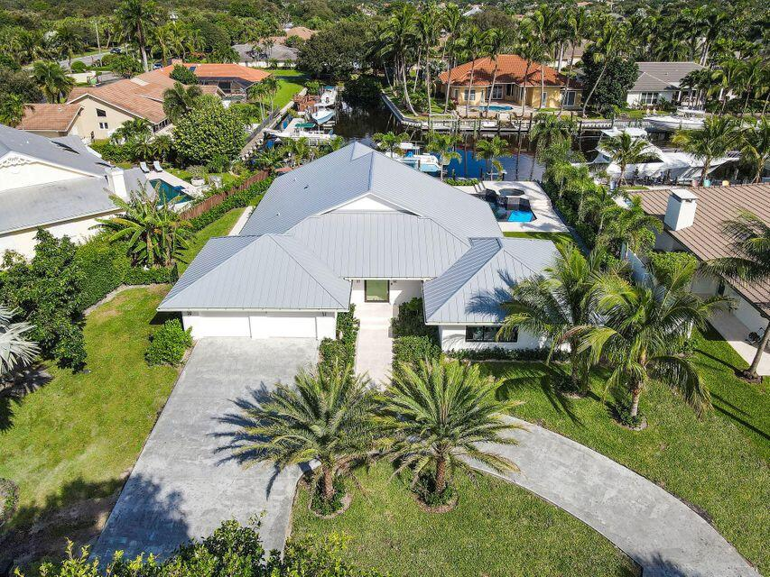 A modern masterpiece; situated along a picturesque canal providing direct access to the intracoastal waterway, this Palm Beach Gardens home's meticulous curb appeal greets residents, presaging the artfully executed modern aesthetic inside. Unfurling back from the waterline, this meticulously finished home, at over 2700 Sq. Ft., is an exercise in artfully executed modern design. The outdoor space is centered around a covered lanai bordered by manicured turf. Just beyond the confines of the backyard rests an expansive private dock with top of the line boat lift is the perfect platform for South Florida's famed marine pursuits. Guests enter to vaulted ceilings and a great room dappled in natural light from floor to ceiling windows opening to the pool deck and waterfront. In keeping with the home's flawlessly executed aesthetic, an open floor plan provides a seamless transition to the home's elegant kitchen and breakfast nook. Best in class appliances, nestled amidst sleek bespoke cabinetry, bolstered by a spacious island with bar seating provide a tasteful compliment to the home's common area. A sprawling master with private entry to a sleekly modeled pool-deck is paired with a spacious en suite; echoing the fit and finish of the kitchen; quality is exuded in every regard.