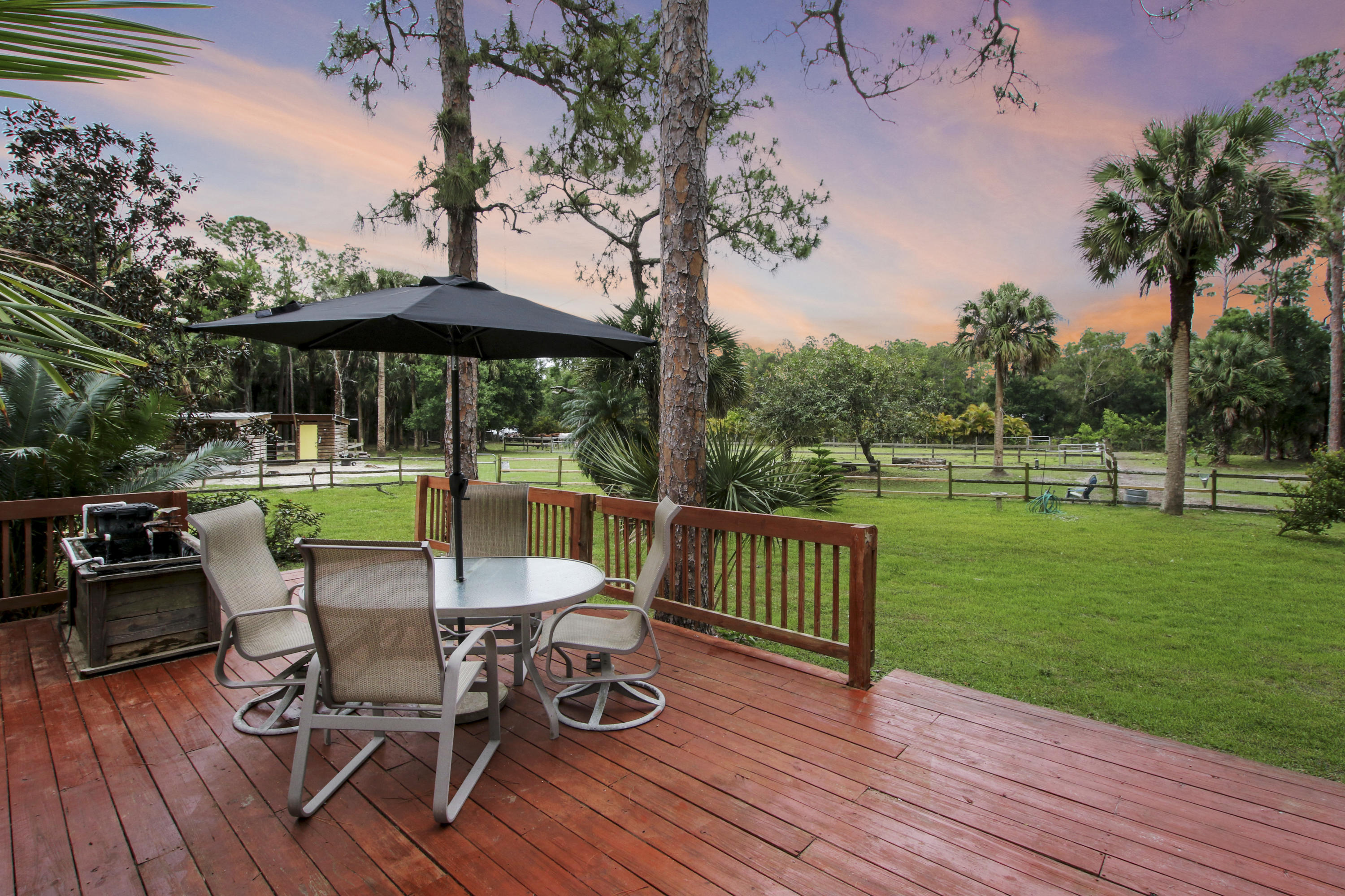 A DREAM COME TRUE for those looking for peace & tranquility on this stunning 5 acre property. Feel worlds away surrounded by the beauty of nature & 20 exotic fruit trees, yet just minutes from parks, shops, restaurants, beach & town. Built in the 1960's, this home exudes charm, warmth & has withstood the test of time. As each owner has upgraded, the original charm & Dade Pine floors/ ceilings remain & are beautiful. Enjoy 4 bedrooms, plus a den & 4 full baths. Master, 2nd bedroom & small studio/den are on 1st floor & 2nd story has 2 bedrooms & 2 full baths. Your horses will love their 6 stall barn w/water & power & 3 shady paddocks to roam & Ag Exemption = Lower taxes. Take a trail ride to Riverbend or stroll 2 blocks to live music next to the fire at Taylor's Farmhouse Cafe! More HERE.. This property is dry! No lake here taking up 1/2 your property. Your seasonal fruits, nuts and herbs include Mango, Ackee, Langdon, Rose apple, Wax apple, Pond apple, Macadamia nut, Brazilian cherry, Star fruit, Bay rum, Kafir Lime, Tamarind, Lemongrass, Awapuhi, Calamondin, Monstera deliciosa, Miracle fruit, Passion fruit & Lemon! Additional upgrades to this absolutely adorable home are freshly painted hardi-plank siding, new AC and all new plumbing under house.   Turn key boarding business also available with income opportunities which includes branded website. Note lower taxes as property currently has Agricultural exemption. New owner will need to reapply for homestead and ag exemption by March 2022.   Additional upgrades to this absolutely adorable home are hardi-plank siding, exterior has been freshly painted, new AC/heat condenser (2020). Also, there are two RV hooks ups on property.